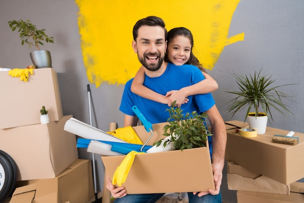 Little daughter hugs her father, who keeps box of tools. Premium Photo