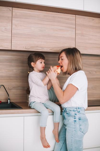작은 딸이 부엌 표면에 앉아 그녀의 어머니가 사과를 시도하도록주는 프리미엄 사진