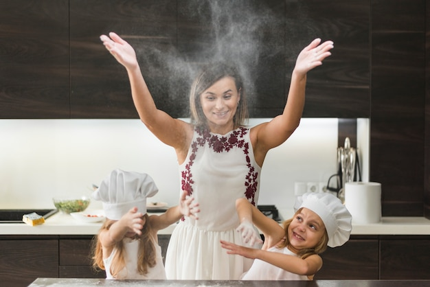 Little daughters with mother throwing flour and having fun while preparing food Free Photo