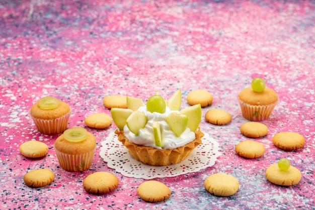 色付きの机の上にスライスしたフルーツクッキーと小さなおいしいケーキ、ケーキ甘い砂糖のカラー写真 無料写真