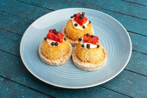 Маленькие вкусные пирожные со сливками и мармеладом сверху внутри синей тарелки на синем Бесплатные Фотографии