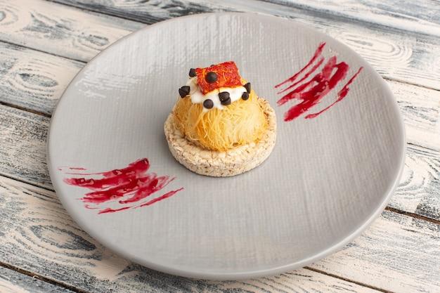 Маленькие вкусные пирожные со сливочными фруктами и мармеладом сверху внутри фиолетовой тарелки на сером Бесплатные Фотографии