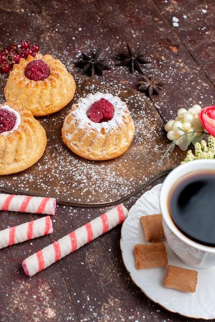 Маленькие вкусные пирожные с малиной вместе с леденцами в стиках, кофе на деревянном столе, торт, сладкие фрукты, выпечка, бисквит, ягода Бесплатные Фотографии