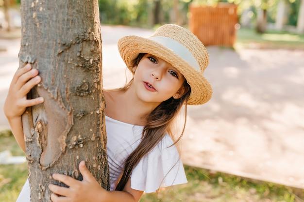 夏の日に公園で遊んでいる間、木の後ろに隠れている小さなファッショナブルな女性。白いリボンと屋外で休暇を過ごすエレガントなドレスと帽子のかなりブルネットの女の子。 無料写真