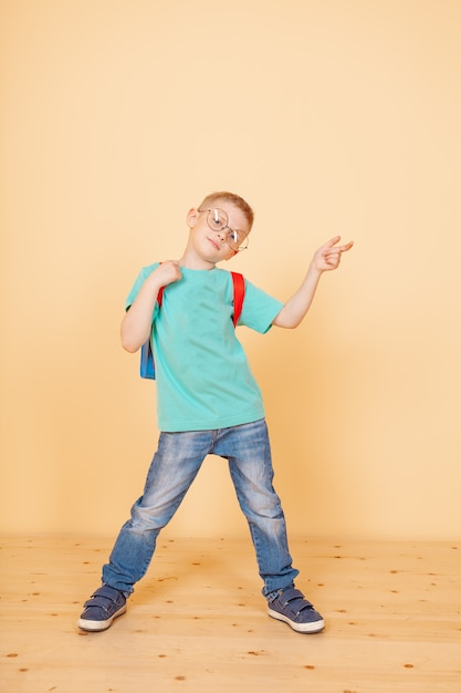 Little funny boy standing with glasses, backpack. surprising. isolated on the yellow. Premium Photo