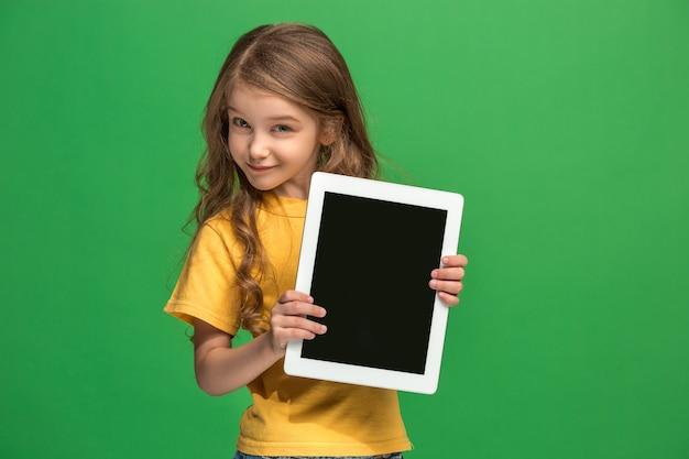 緑のスタジオの背景にタブレットを持つ小さな面白い女の子。彼女は何かを見せて画面を指さしている。 無料写真