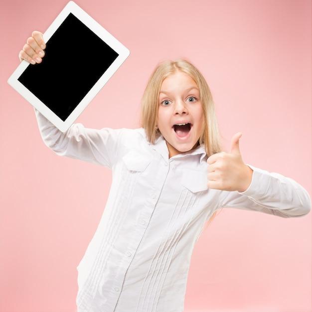 Piccola ragazza divertente con tablet su sfondo rosa studio. mostra qualcosa e indica lo schermo. Foto Gratuite