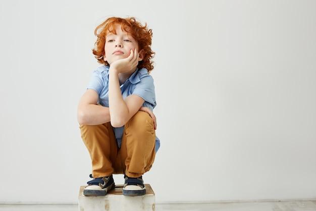 Маленький смешной рыжий ребенок сидит, держа голову рукой Бесплатные Фотографии
