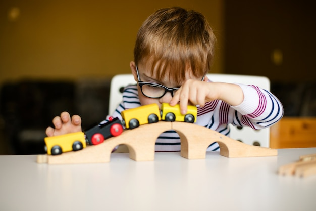 Little ginger child boy in the glasses with syndrome dawn playing with wooden railways Premium Photo