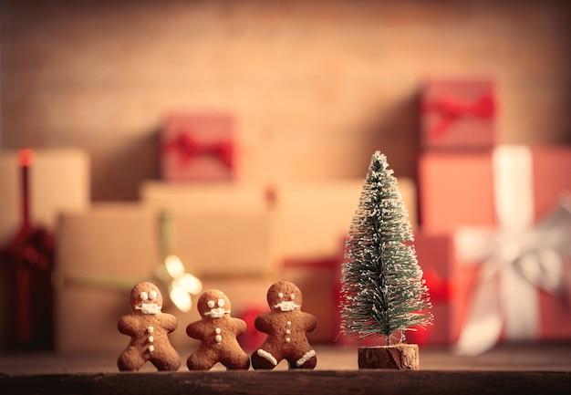 小さなジンジャーブレッドマンと背景に贈り物とテーブルの上のクリスマスツリー Premium写真