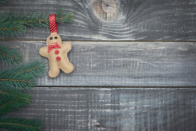 Omino di pan di zenzero che appende sul ramo di pino Foto Gratuite