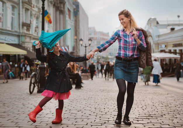 Little girl 6 years old child with an umbrella in rubber boots having fun with her mother on a bench in the center of moscow in the fall or spring. Premium Photo