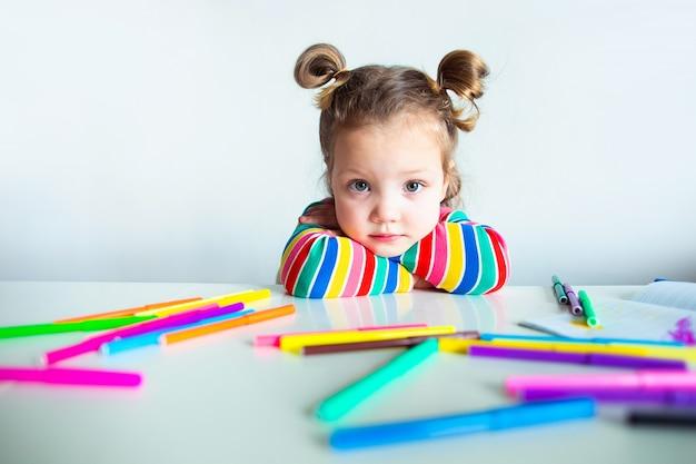 Маленькая девочка, 3-х летняя девочка, с прической в хвостике в разноцветной полосатой куртке на светлой стене за столом, рисует разноцветные маркеры и улыбается Premium Фотографии