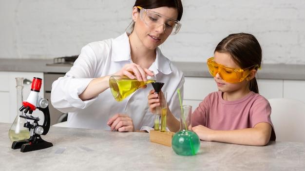 현미경 및 시험관으로 과학 실험을하는 어린 소녀와 여성 교사 무료 사진