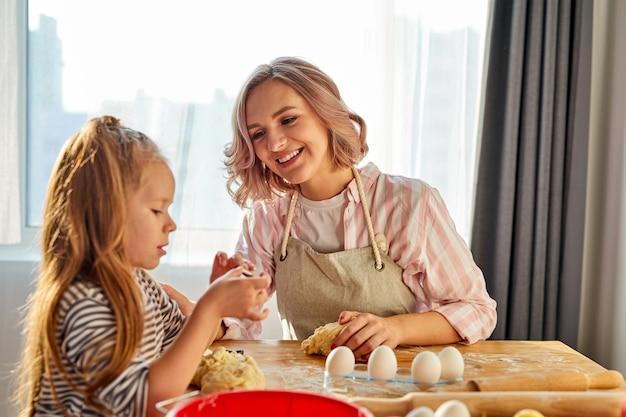 キッチンで生地をこねるエプロンの少女と彼女のお母さん、パン、ピザ、またはクッキーを焼くための自家製ペストリー。家族の楽しさと料理のコンセプト Premium写真