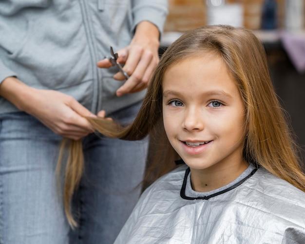 彼女の美容師との約束で散髪をしている少女 Premium写真