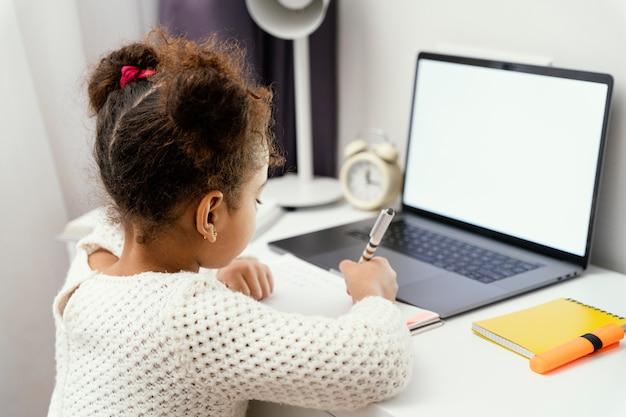 Bambina che frequenta la scuola in linea a casa utilizzando il computer portatile Foto Gratuite