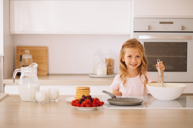 Little girl baking pancakes at the kitchen Free Photo