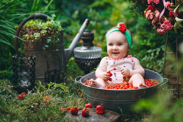 A little girl bathes in a basin with strawberries in the garden. Premium Photo