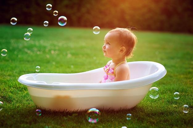 Little girl bathes in a bath with soap bubbles Premium Photo