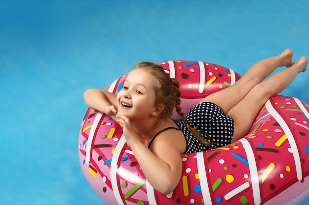 Little girl in a bathing suit lying on a donut inflatable circle. Premium Photo