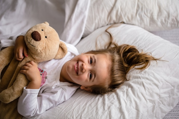 Little girl in bed with soft toy the emotions of a child Free Photo