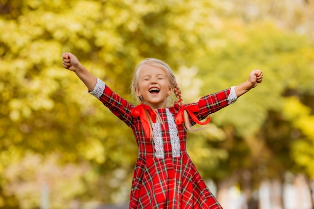 Little girl blonde first grader red plaid dress smiling in the street Premium Photo