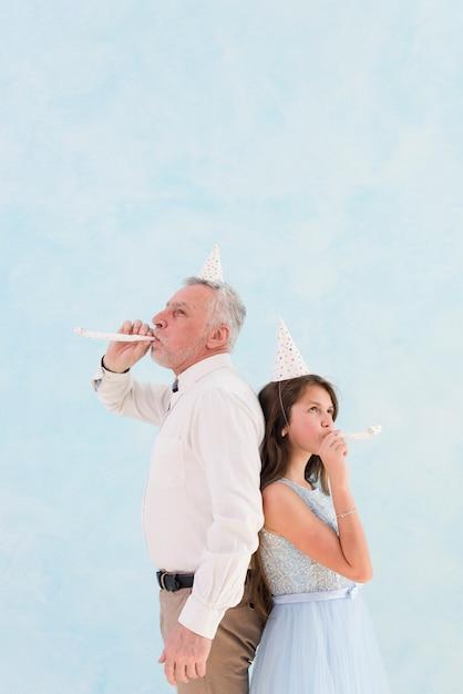 Воздуходувка дует маленькая девочка с дедушкой во время празднования Бесплатные Фотографии