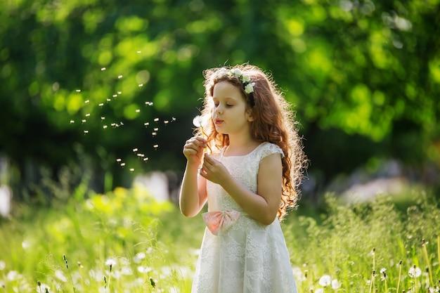 Little girl blowing white dandelion in meadow. Premium Photo