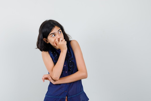 Little girl in blue blouse holding hand on mouth, looking up and looking curious , front view. Free Photo