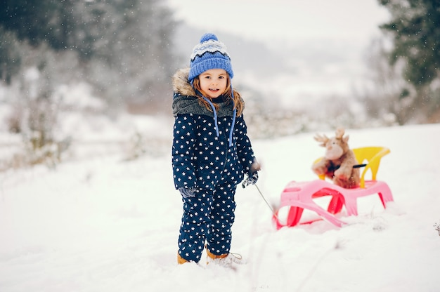 Little girl in a blue hat playing in a winter forest Free Photo