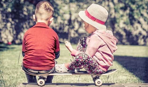 Bambina e ragazzo giocando su skateboard, contro nel giardino verde, il concetto di amicizia d'infanzia Foto Gratuite
