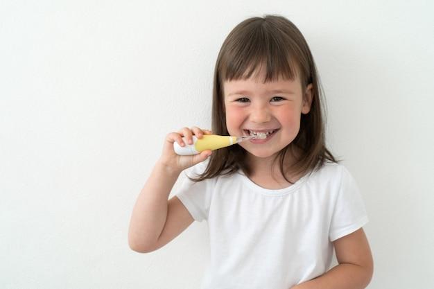 Little girl brushes her teeth herself Premium Photo