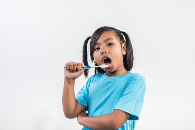 Little girl brushing her teeth in studio shot Free Photo