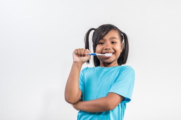 Bambina che pulisce i suoi denti nel colpo dello studio Foto Gratuite