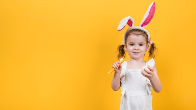 Little girl in bunny ears with egg and felt pen Free Photo