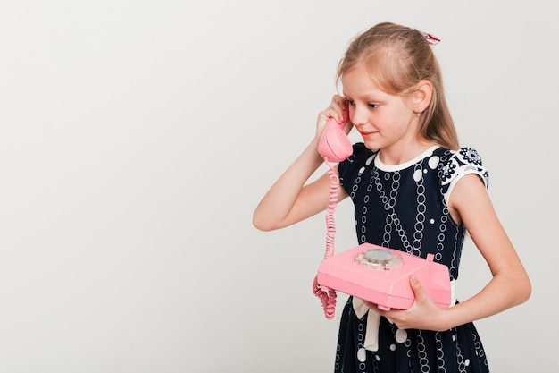 Little girl calling on vintage telephone Free Photo