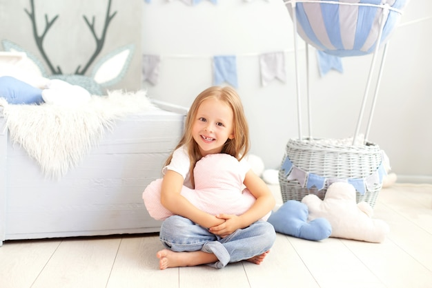 A little girl in casual clothes holds a cloud pillow against the wall of a decorative balloon. the child plays in children room. the concept of childhood, travel. birthday, holiday decorations Premium Photo