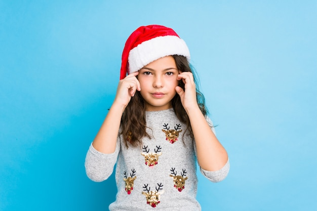 Little girl celebrating christmas day focused on a task, keeping forefingers pointing head. Premium Photo