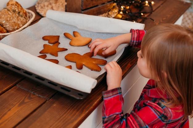 Bambina che controlla i biscotti di natale al forno Foto Gratuite