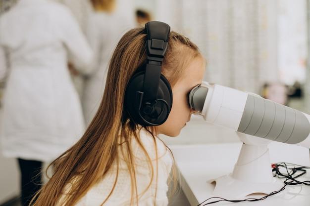 Маленькая девочка проверяет свое зрение в центре офтальмологии Бесплатные Фотографии