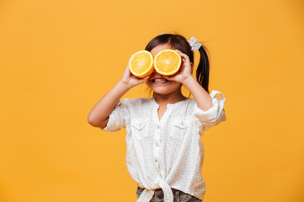 Little girl child covering eyes with orange. Free Photo