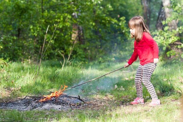 Little girl child in forest playing with bonfire. Premium Photo