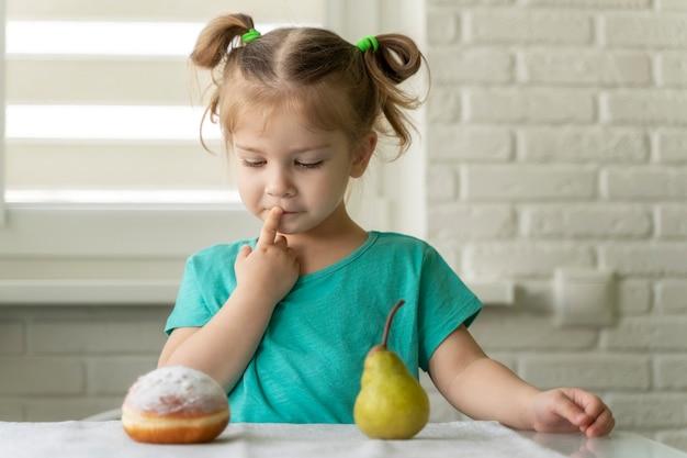 Маленькая девочка выбирает между пончиком и фруктами. Premium Фотографии