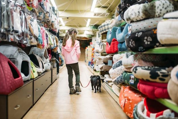 어린 소녀는 애완 동물 가게에서 강아지 집을 선택 프리미엄 사진