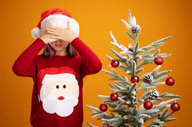 Bambina in maglione di natale e cappello da babbo natale chiudendo gli occhi con le mani accanto a un albero di natale su sfondo arancione Foto Gratuite