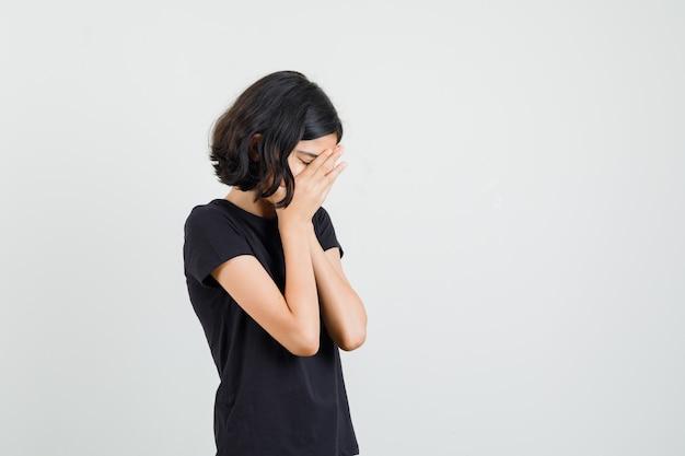Bambina che stringe le mani sul viso in maglietta nera e sembra triste. vista frontale. Foto Gratuite