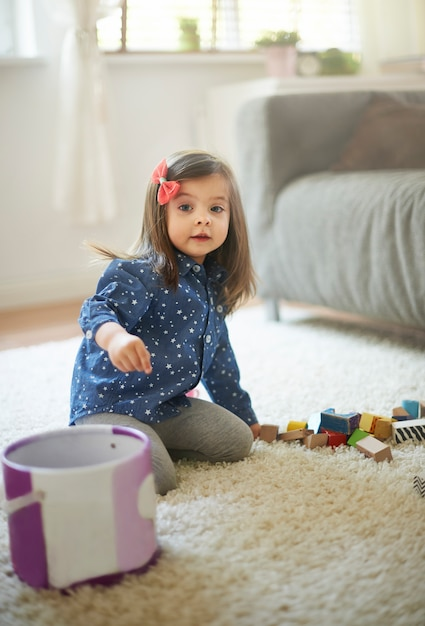 Little girl cleaning blocks after the playing Free Photo
