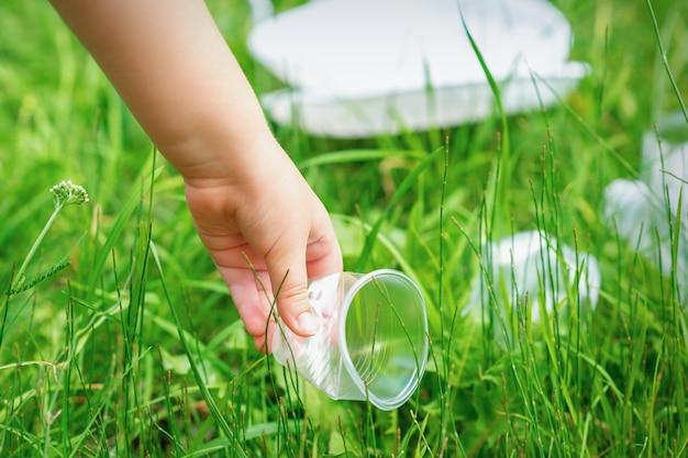 Маленькая девочка чистит пластиковую посуду на зеленой траве в парке Premium Фотографии