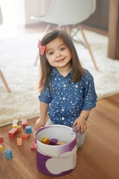 Little girl cleans up after the playing Free Photo
